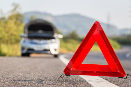 broken car: Red emergency stop sign and broken silver car on the road Stock Photo
