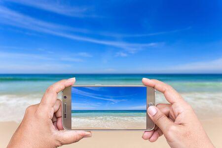 Cierre de la mano de la mujer que sostiene teléfono inteligente y tomar foto de vista