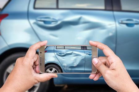 Bliska ręce kobiety gospodarstwa smartphone i wziąć fotografię wypadku samochodowym