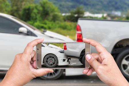 여성이 들고 스마트 폰의 손을 닫고 자동차 사고의 사진을 촬영 스톡 콘텐츠