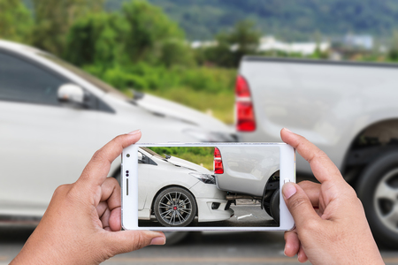 two car garage: Close up hand of woman holding smartphone and take photo of car accident