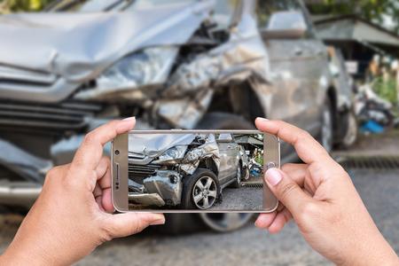 Schließen Sie die Hand der Frau mit Smartphone und nehmen Sie Foto Autounfall Lizenzfreie Bilder