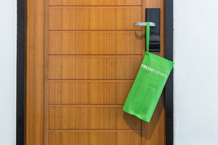 accommodation space: Green textile bag with newspaper hang on the door in hotel