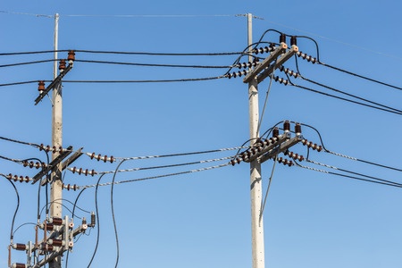 amperage: Electric pole connect high voltage electric wires on blue sky background