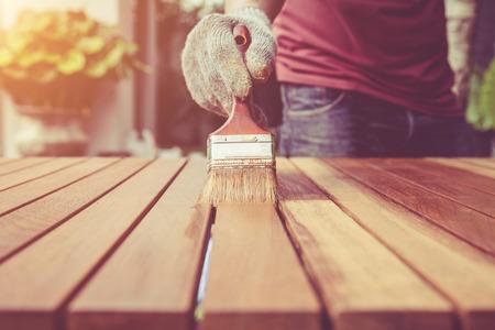 Sluit de penseel in de hand en verf op de houten tafel. Retro en vintage stijl Stockfoto