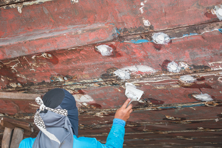 barnacles: A woman worker filling wood filler under fishing boat Stock Photo