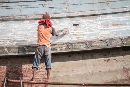 hull: Boat Hull repairs A man using grinder in preparation for anti foul paint being applied Stock Photo