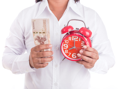 Woman holding Thai money and red alarm clock isolated on white background. Buy some time concept