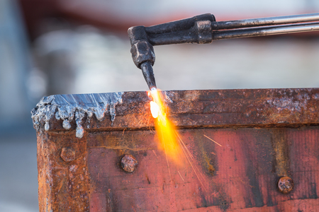 A worker cutting steel using metal torch Stock Photo