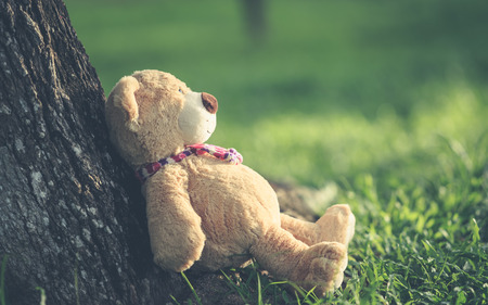 tiny lenses: Close up lovely brown teddy bear sitting on grass field with lens flare. Warm toning effect. Retro and vintage style Stock Photo