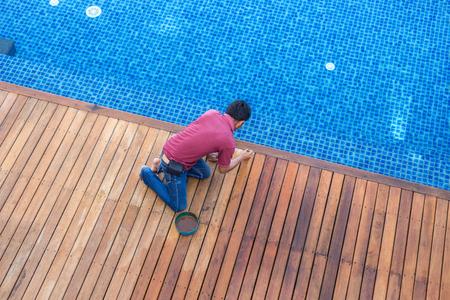 Een werknemer schilderij buitenmuur houten zwembad dek, Bovenaanzicht