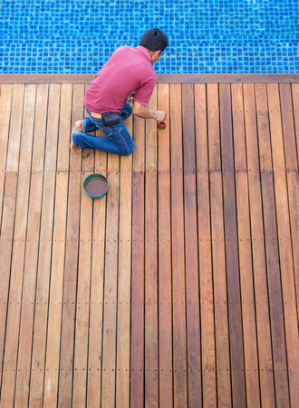 A worker painting exterior wooden pool deck, Top view