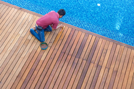 A worker painting exterior wooden pool deck, Top view Stok Fotoğraf - 60636059