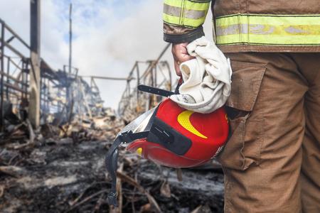 흰색 배경에 고립 된 빨간색 안전 헬멧을 들고 소방 관을 닫습니다 스톡 콘텐츠