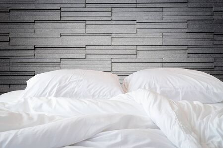 messy room: Close up white bedding sheets and pillow on natural stone wall room background, Messy bed concept Stock Photo
