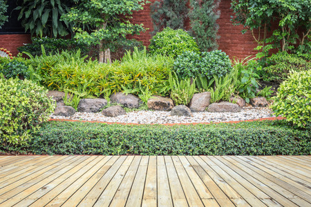 decking: Old hardwood decking or flooring and green plant in garden decorative Stock Photo