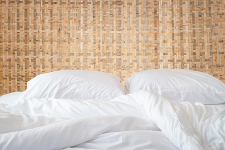 messy room: Close up white bedding sheets and pillow on wooden wall room background, Messy bed concept