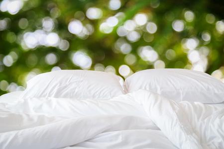 Close-up witte beddengoed lakens en kussen en abstracte van vage lichte achtergrond Stockfoto