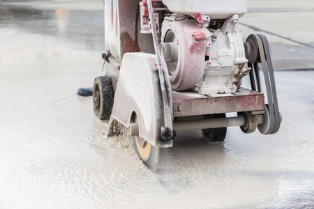saw blade: A worker cutting concrete road with diamond saw blade machine