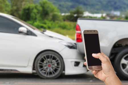 fender bender: Close up hand of woman holding smartphone and take photo of car accident