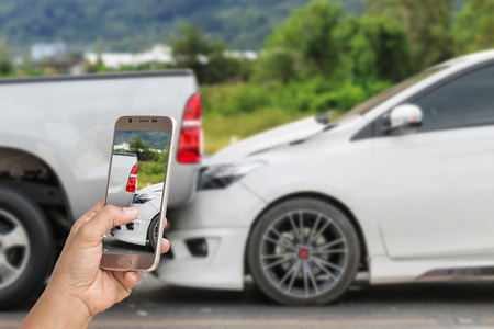 rear end: Close up hand of woman holding smartphone and take photo of car accident