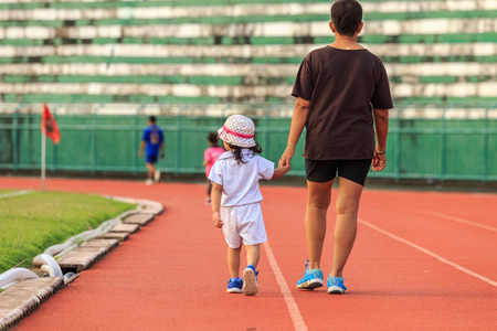 A mother holding her daughter hand and walking in running track