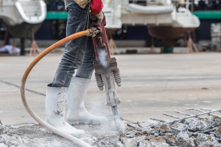 Construction worker removes excess concrete with drilling machine in construction site