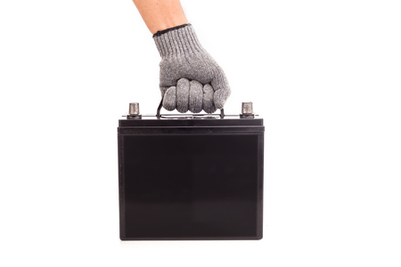 Close up hand holding black car battery isolated on white background