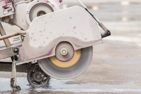A worker cutting concrete road with diamond saw blade machine
