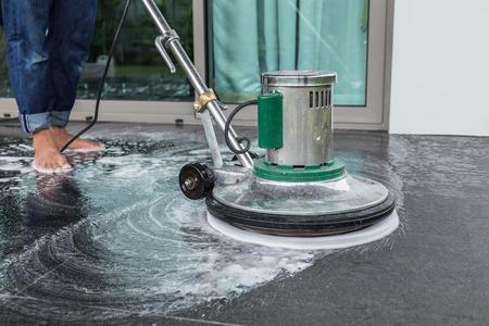 Buitenkant zwarte stenen vloer reiniging met polijsten machine en chemische