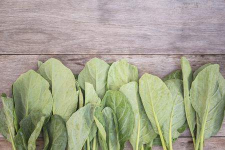 kana: Top view green fresh Gai lan (Chinese broccoli) on wooden plank Stock Photo