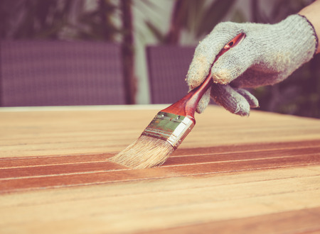 Close up paintbrush in hand and painting on the wooden table. Retro and vintage style Stock Photo