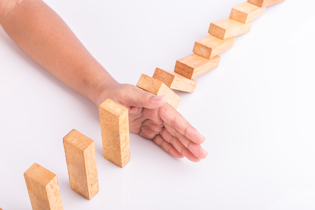 fragile economy: Close up hand stop wooden block. Domino risk effect concept Stock Photo