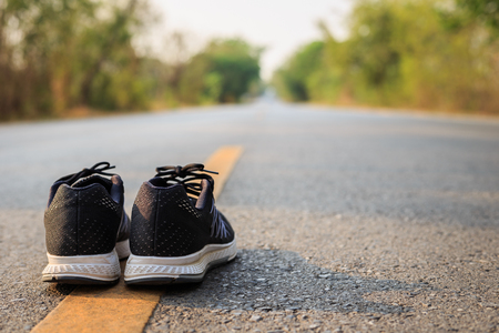 Close up new black running shoes on asphalt road in morning time