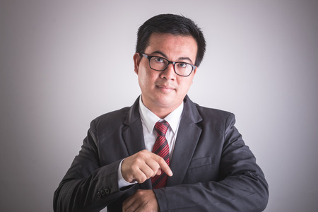 lack of confidence: Portrait of Asian businessman with hand point on his wrist. Time checking or punctually concept. Studio shot on grey background