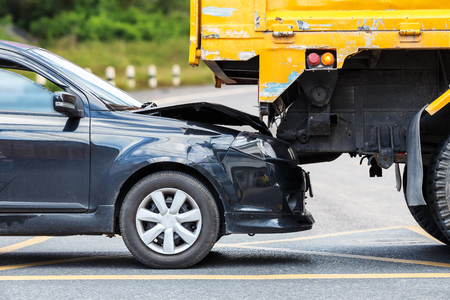 involving: Accident on the road involving black car and yellow truck in Phuket, Thailand Stock Photo