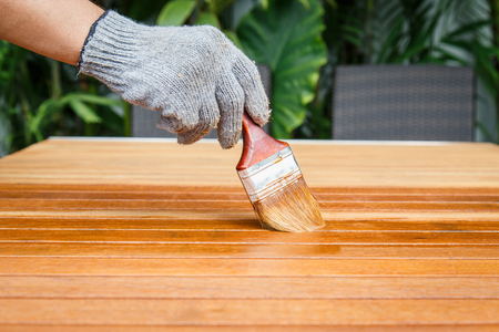 carpenter's bench: Brush in hand and painting on the wooden table Stock Photo