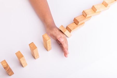 Close up hand stop wooden block. Domino risk effect concept Stock Photo
