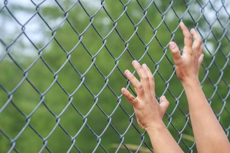 Close up hands hanging on metal chain link fence Reklamní fotografie
