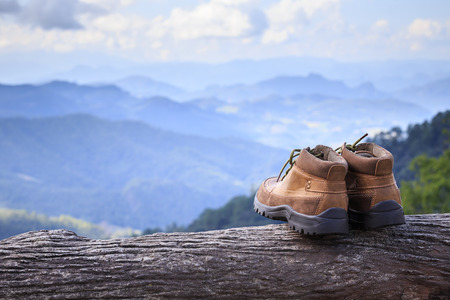 Close up new brown leather shoe on mountain view point. Adventure concept