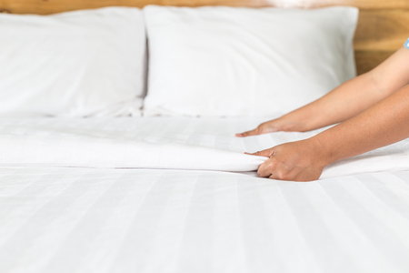 bedclothes: Close up hand set up white bed sheet in hotel room Stock Photo