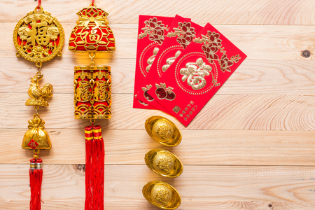 Top view gold and red Chinese new year decoration on wooden background.  Translation in English meaning lucky and richly Stock Photo