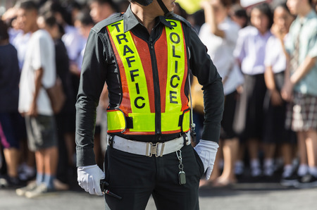 Traffic police standing on the road while doing his work