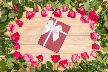 Top view fresh pink rose flower and gift box on wooden deck. For love or valentine day concept Stock Photo