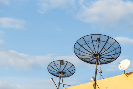 Several satellite dish installed on the house roof with blue sky background Banco de Imagens