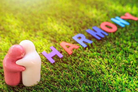White and pink ceramic doll on green grass with wood text HARMONY word. Use for harmony day concept