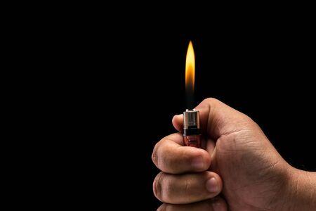 gas lighter: Close up hand holding burning gas lighter. Studio shot isolated on black background