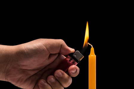 Close up hand holding burning gas lighter to light candle. Studio shot isolated on black background