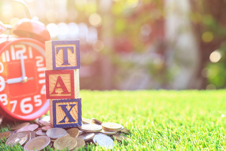 TAX write in color alphabet wood box on stack of Thai baht coin and red alarm clock with right free space for text. For time to pay tax concept. Shot in morning with sunlight and lens flare effect Stock Photo