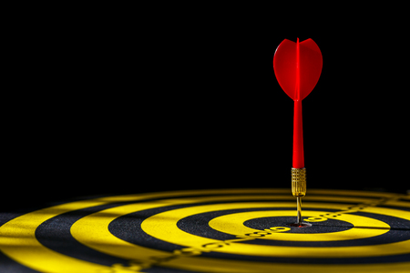Close up red dart arrow in the center of dartboard. Isolated on black background